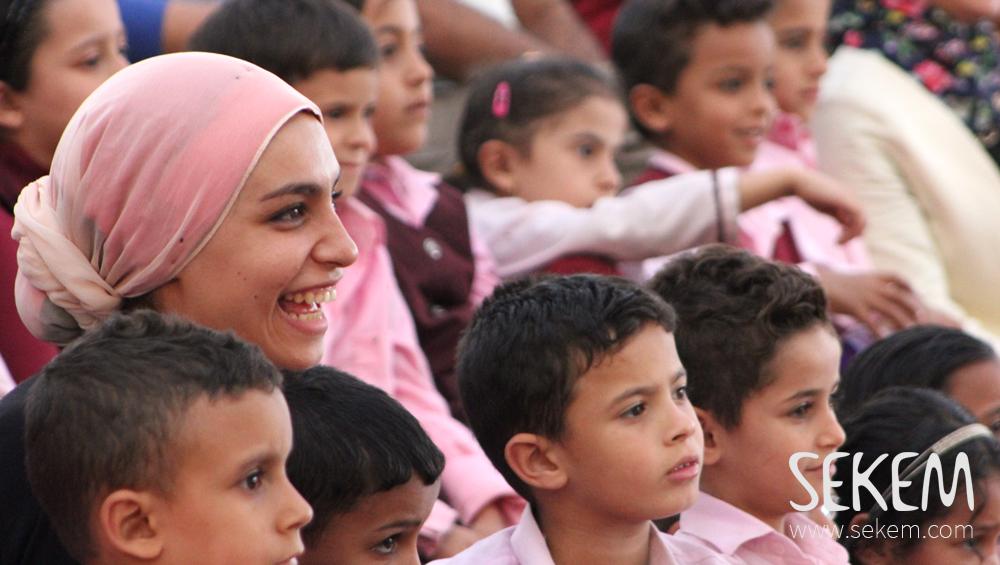 SEKEM Schüler beobachten aufmerksam das Bühnengeschehen.