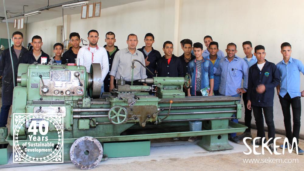 Die Auszubildenden in SEKEMs Metallwerkstatt hinter der neuen Maschine.